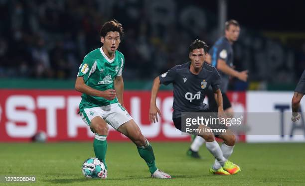 Yuya Osako of Werder Bremen and Lucas Stauffer of Jena vie for the ball during the DFB Cup first round match between FC Carl Zeiss Jena and Werder...
