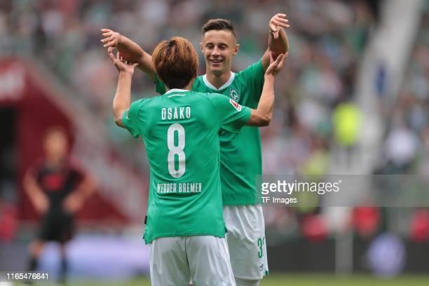 Yuya Osako of Werder Bremen and Marco Friedl of Werder Bremen celebrate after scoring his team's third goal during the Bundesliga match between SV...