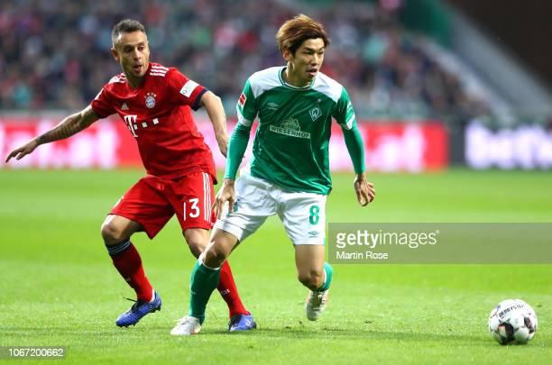 Yuya Osako of Werder Bremen is challenged by Rafinha of Bayern Munich during the Bundesliga match between SV Werder Bremen and FC Bayern Muenchen at...