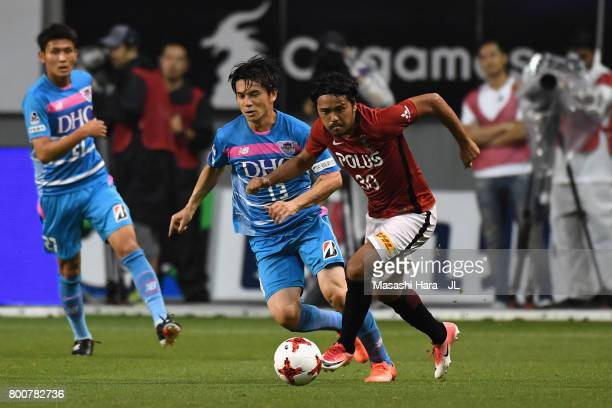 Yuzo Kobayashi of Sagan Tosu and Shinzo Koroki of Urawa Red Diamonds compete for the ball during the JLeague J1 match between Sagan Tosu and Urawa...