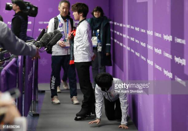 Yuzuru Hanyu of Japan kneels past Shoma Uno who is interviewed after a training session on day six of the PyeongChang Winter Olympic Games at...