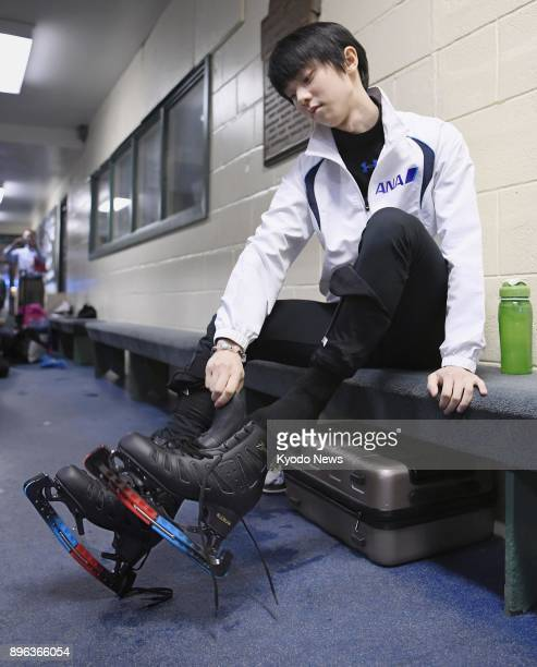 Yuzuru Hanyu of Japan puts on his skates ahead of a practice session in Toronto his training base in August 2017 ==Kyodo