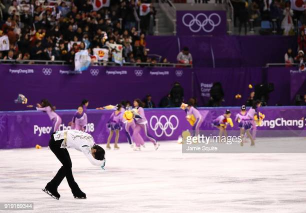 Yuzuru Hanyu of Japan reacts after competing as fans throw gifts and hold Japanese flags during the Men's Single Free Program on day eight of the...