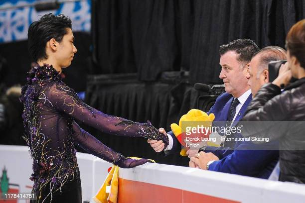Yuzuru Hanyu of Japan shake's his coach's hand before performing in the mens free skating placing first with a score of 21299 during the ISU Grand...