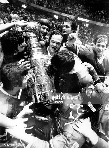 Yvan Cournoyer of the Montreal Canadiens center holds the Stanley Cup Trophy as he watches his teammates celebrate and kiss the trophy after they...