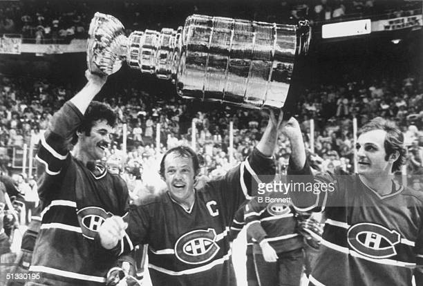 Yvan Cournoyer of the Montreal Canadiens, hoist the Stanley Cup Trophy with help from teammates Yvon Lambert and Guy Lafleur after defeating the...