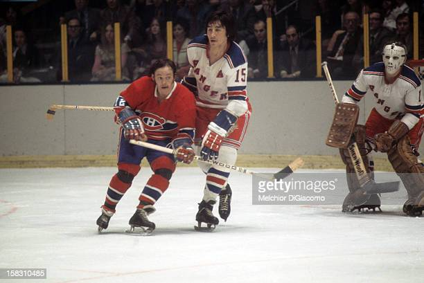 Yvan Cournoyer of the Montreal Canadiens is defended by Jim Neilson of the New York Rangers as goalie Ed Giacomin of the Rangers defends the net...