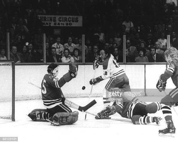 Yvan Cournoyer of the Montreal Canadiens shoots as goalie Tony Esposito of the Chicago Blackhawks makes the save during their game circa 1970's at...