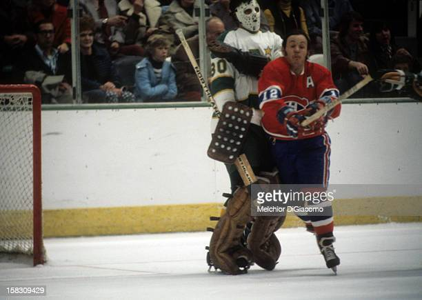 Yvan Cournoyer of the Montreal Canadines crashes into goalie Cesar Maniago of the Minnesota North Stars during their game circa 1972 at the Met...