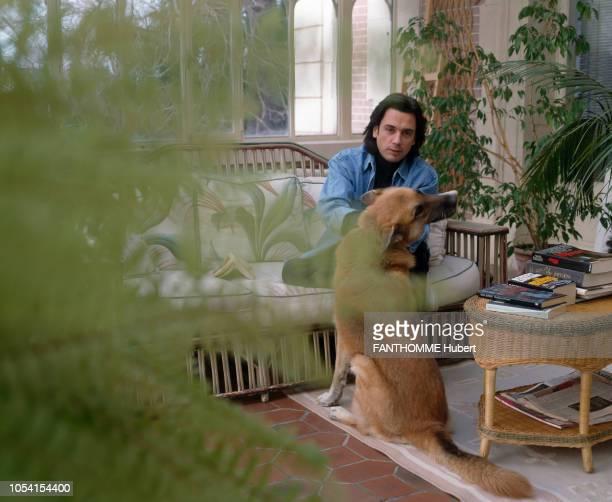 Yvelines France Décembre 1991 Le musicien JeanMichel JARRE dans sa maison de CroissysurSeine Ici posant dans son jardin d'hiver assis au milieux de...