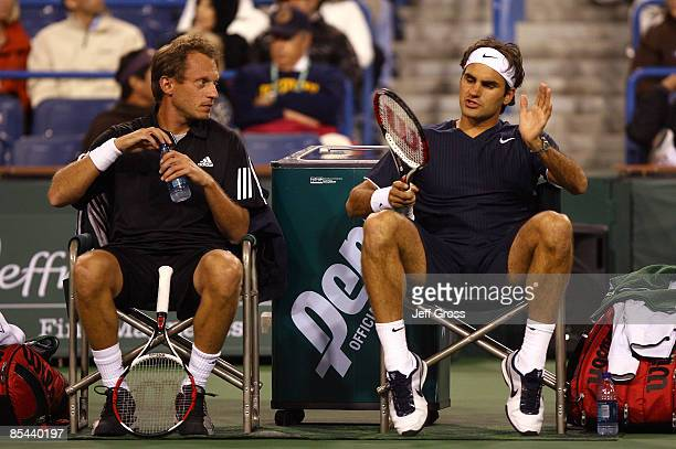 Yves Allegro and Roger Federer of Switzerland converse during a changeover against Bob Bryan and Mike Bryan during the BNP Paribas Open at the Indian...