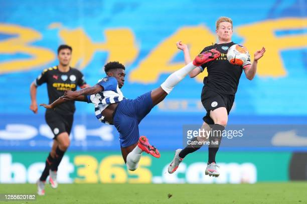 Yves Bissouma of Brighton and Hove Albion and Kevin De Bruyne of Manchester City clash whilst jumping for the ball during the Premier League match...