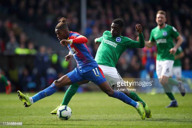 Yves Bissouma of Brighton and Hove Albion battles for possession with Wilfried Zaha of Crystal Palace during the Premier League match between Crystal...