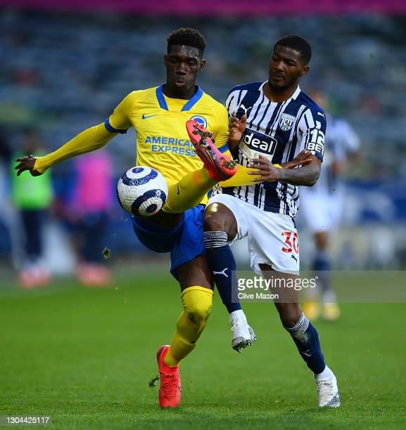 Yves Bissouma of Brighton and Hove Albion is challenged by Ainsley Maitland-Niles of West Bromwich Albion during the Premier League match between...