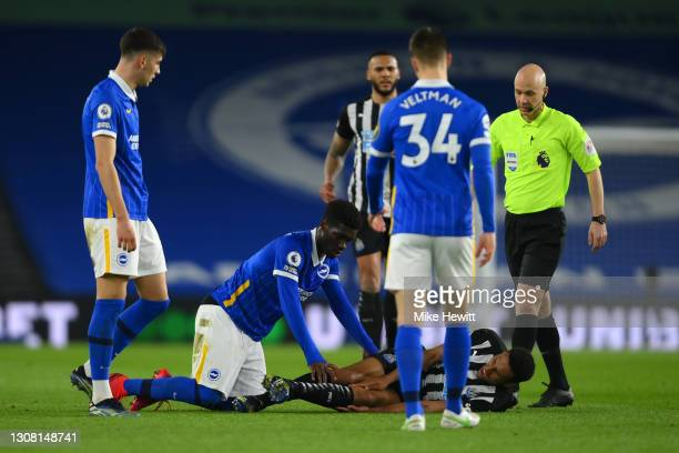 Yves Bissouma of Brighton & Hove Albion checks on Isaac Hayden of Newcastle United who reacts with an injury during the Premier League match between...