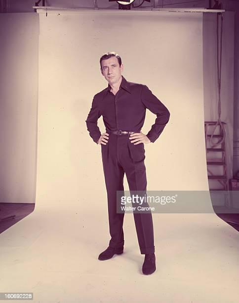 Yves Montand Lors d'une scéance en studio l'acteur Yves MONTAND en pantalon et chemise noirs se tient debout les mains posées sur ses hanches devant...
