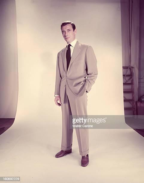 Yves Montand Lors d'une scéance en studio l'acteur Yves MONTAND en costume grisclair et cravate noire se tient debout la main gauche dans la poche de...