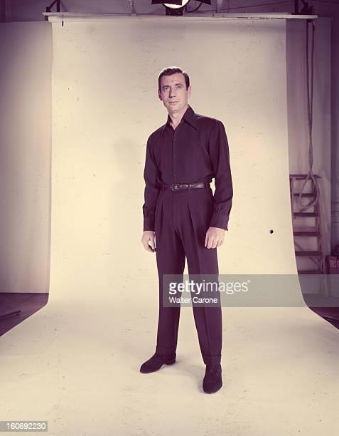 Yves Montand Portrait en studio de l'acteur Yves MONTAND debout en pantalon et chemise noirs devant un fond blanc