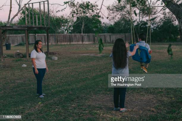 Yvette Arroyo watches her children play in her backyard located next to the Rio Grande levee in Brownsville, Texas on December 04, 2019.