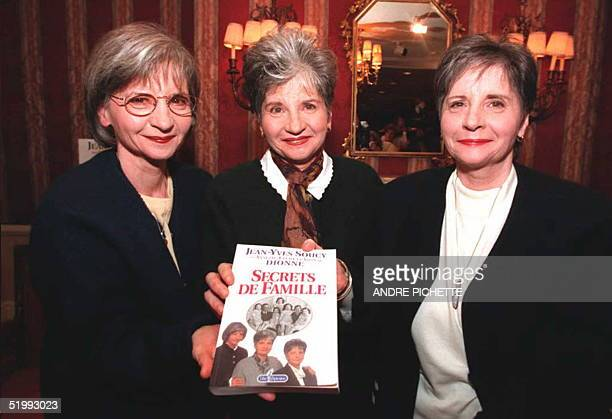 Yvonne Audette and Cecil Dionne hold up a copy of their autobiography Secrets de Famille during a book party in Montreal 02 October They are the...
