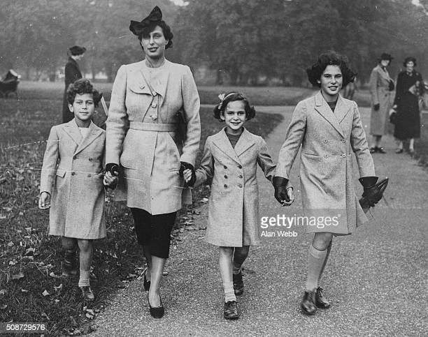 Yvonne Cahen d'Anvers wife of British banker Anthony de Rothschild holding hands with their children Evelyn Anne and Renee as they stroll through...