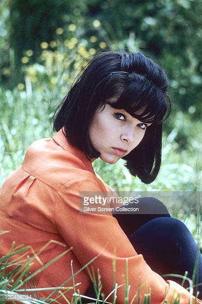 Yvonne Craig US actress weaing an orange blouse sitting on a patch of grass circa 1955