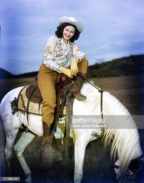 Yvonne De Carlo Canadian actress dressed in western clothing with a cowboy hat and boots as she poses on the back of a white horse circa 1950