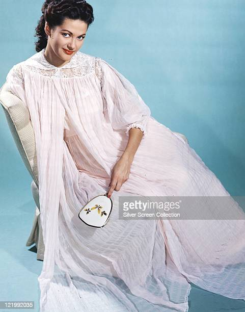 Yvonne De Carlo Canadian actress wearing a long white nightdress holding a mirror in a studio portrait against a blue background circa 1950