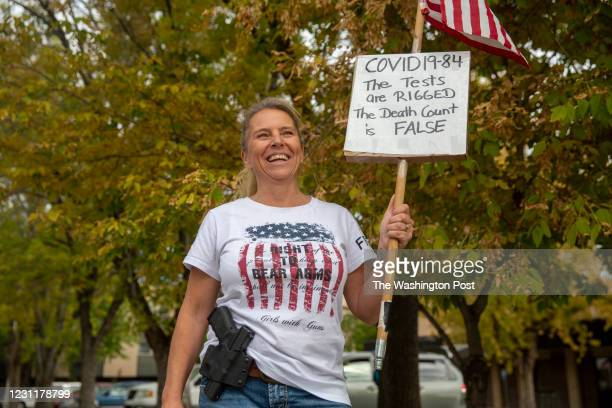 Yvonne Donat, a woman of German descent who lives in Whitehall, MT, waves an American flag and participates in an anti-mask protest down the street...