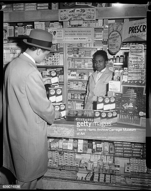 Yvonne Larkins behind counter at pharmacy with man looking at 'REM Cough Medicine' and advertisement for Mary Dee WHOD Radio Show in background circa...