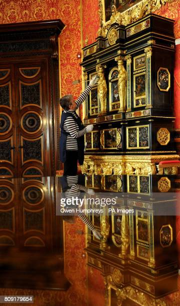 Yvonne Losh a member of the household staff at Alnwick Castle, Northumberland, cleans the world's only pair of ÔSun King' Cucci Cabinets,...