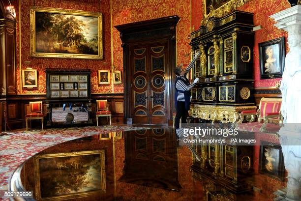 Yvonne Losh a member of the household staff at Alnwick Castle Northumberland cleans the world's only pair of OcircSun King' Cucci Cabinets...