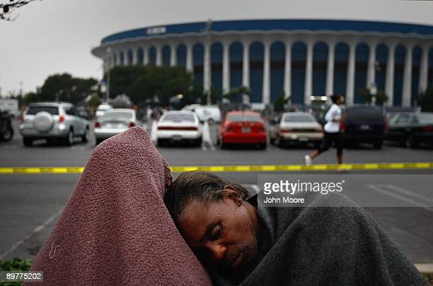 Yvonne McCullough and Anthony Walker sleep while waiting outside to enter a free health clinic at the Forum arena on August 13, 2009 in Inglewood,...