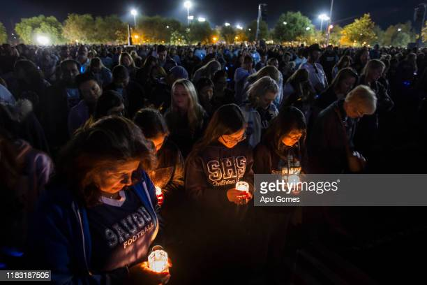 Yvonne Pane Danielle Pane AnhThi Ta and Ha Trinh pray while holding candles at a vigil held for shooting victims on November 17 2019 in Santa Clarita...