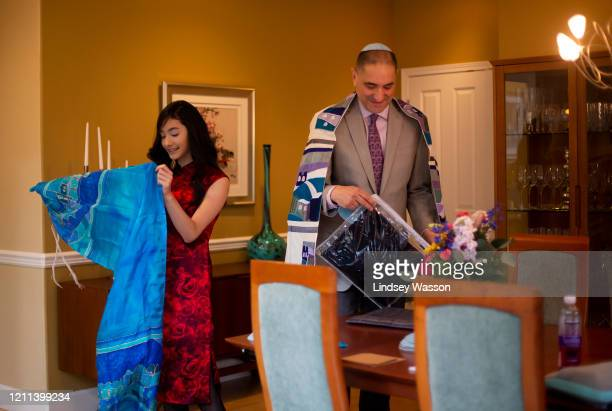 Yvonne Reiter unfolds her tallit a traditional Jewish prayer shawl as she and her father Tsvi Reiter prepare for her bat mitzvah ceremony at home...