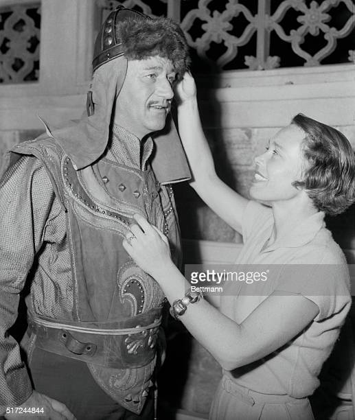 Yvonne Wood top flight studio costume designer puts the finishing touches on john Wayne's getup for a film version of life of Ghengis Khan Miss Wood...