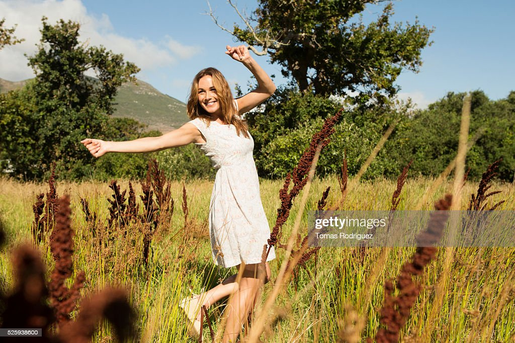Yyoung woman among field at sunny day : Foto de stock
