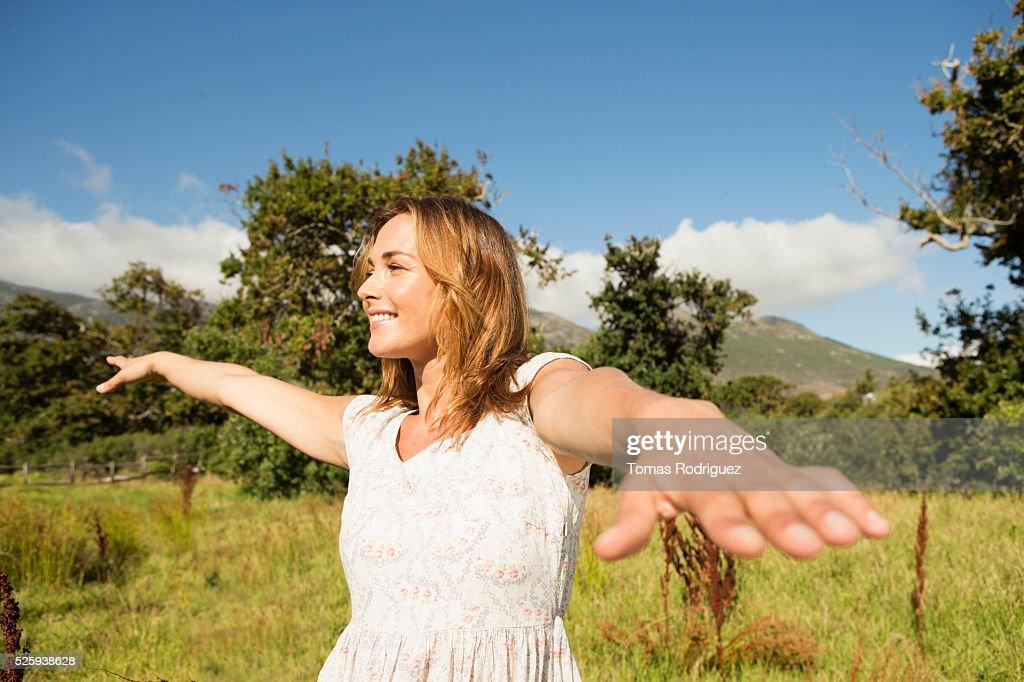 Yyoung woman among field at sunny day : Stock Photo