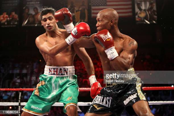 RL Zab Judah connects with a punch to the head of Amir Khan during their super lightweight world championship unification bout at Mandalay Bay Events...