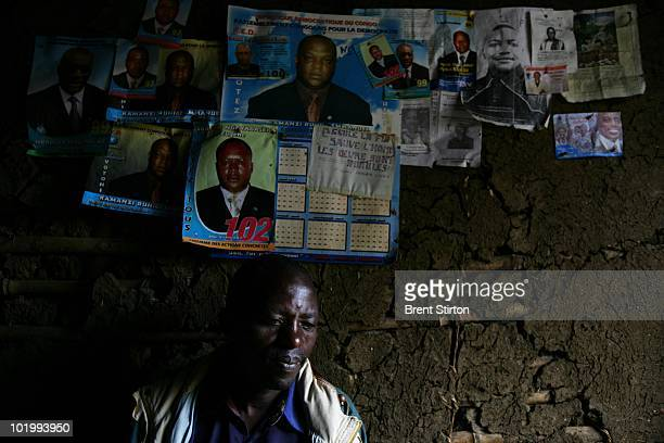 Zabonimba Mbunyimbuya sits in his home underneath a series of posters of politicans who appear to be able to do nothing to curb the ongoing violence...