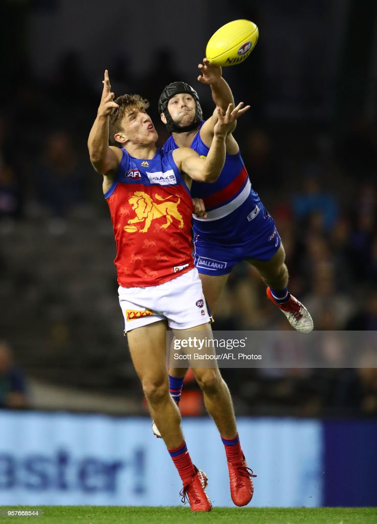 Zac Bailey of the Lions and Caleb Daniel of the Bulldogs compete for the ball during the round eight AFL match between the Western Bulldogs and the Brisbane Lions at Etihad Stadium on May 12, 2018 in Melbourne, Australia.