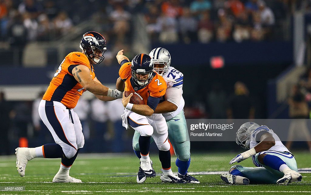 Zac Dysert #2 of the Denver Broncos is sacked by Zach Minter #79 of the Dallas Cowboys in the second half of a preseason game at AT&T Stadium on August 28, 2014 in Arlington, Texas.