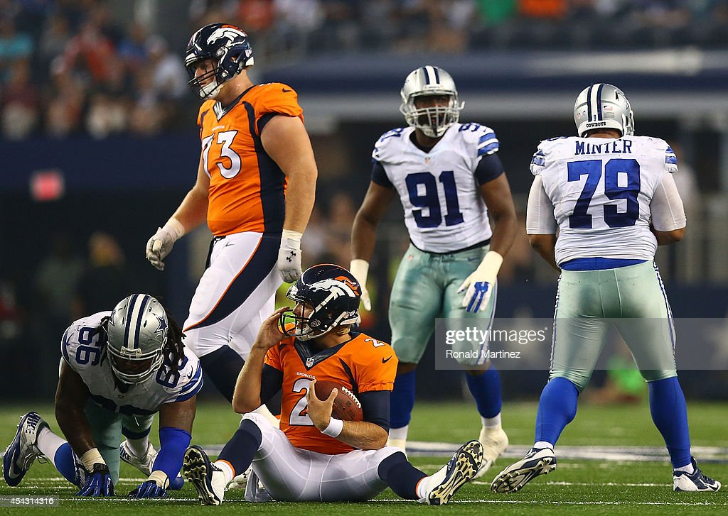 Zac Dysert #2 of the Denver Broncos sits on the ground after being sacked by Zach Minter #79 of the Dallas Cowboys in the second half of a preseason game at AT&T Stadium on August 28, 2014 in Arlington, Texas.