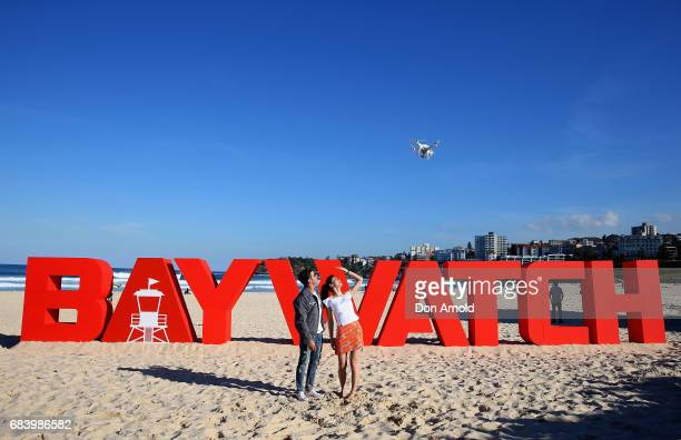Zac Efron and Alexandra Daddario watch a drone fly over head during a photo call for Baywatch on May 17 2017 in Sydney Australia
