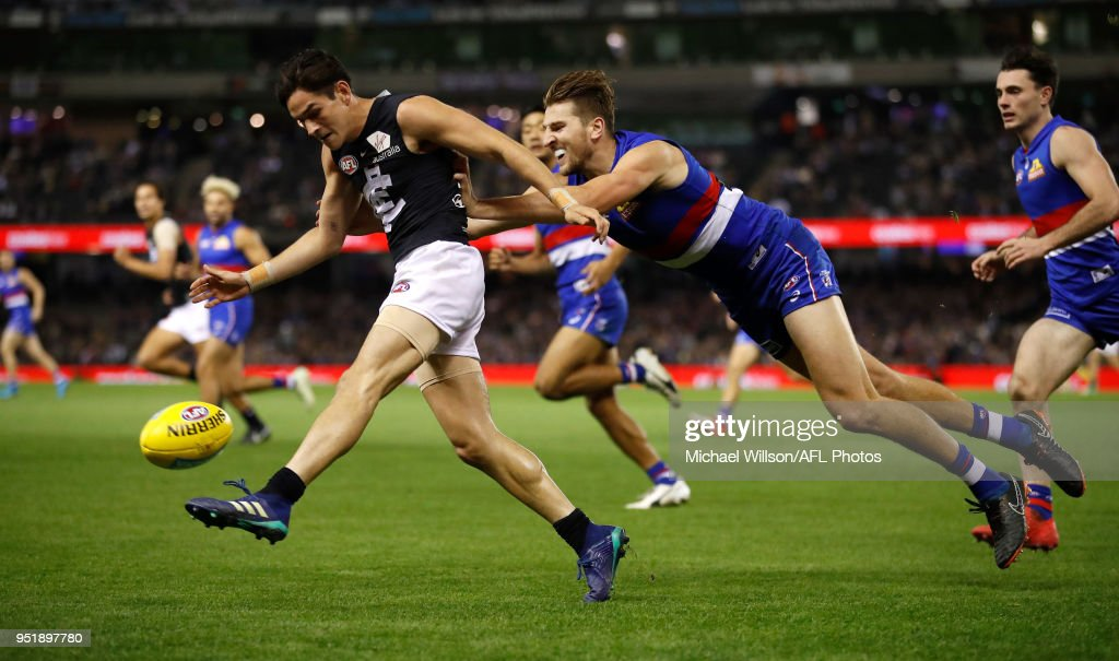Zac Fisher of the Blues is tackled by Marcus Bontempelli of the Bulldogs during the 2018 AFL round six match between the Western Bulldogs and the Carlton Blues at Etihad Stadium on April 27, 2018 in Melbourne, Australia.