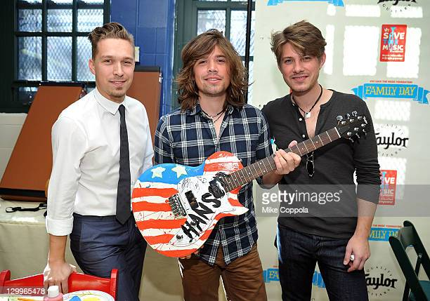 Zac Hanson Taylor Hanson and Isaac Hanson of the band Hanson hold a guitar painted by the band during the VH1 Save the Music Foundation Family Day at...