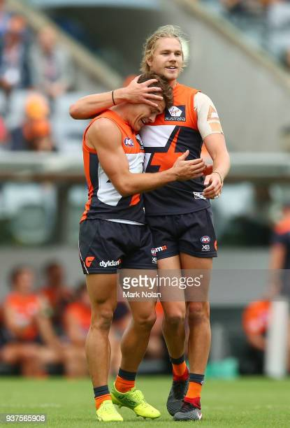 Zac Langdon of the Giants is congratulated by team mate Harrison Himmelberg after kicking is his first goal on debut during the round one AFL match...