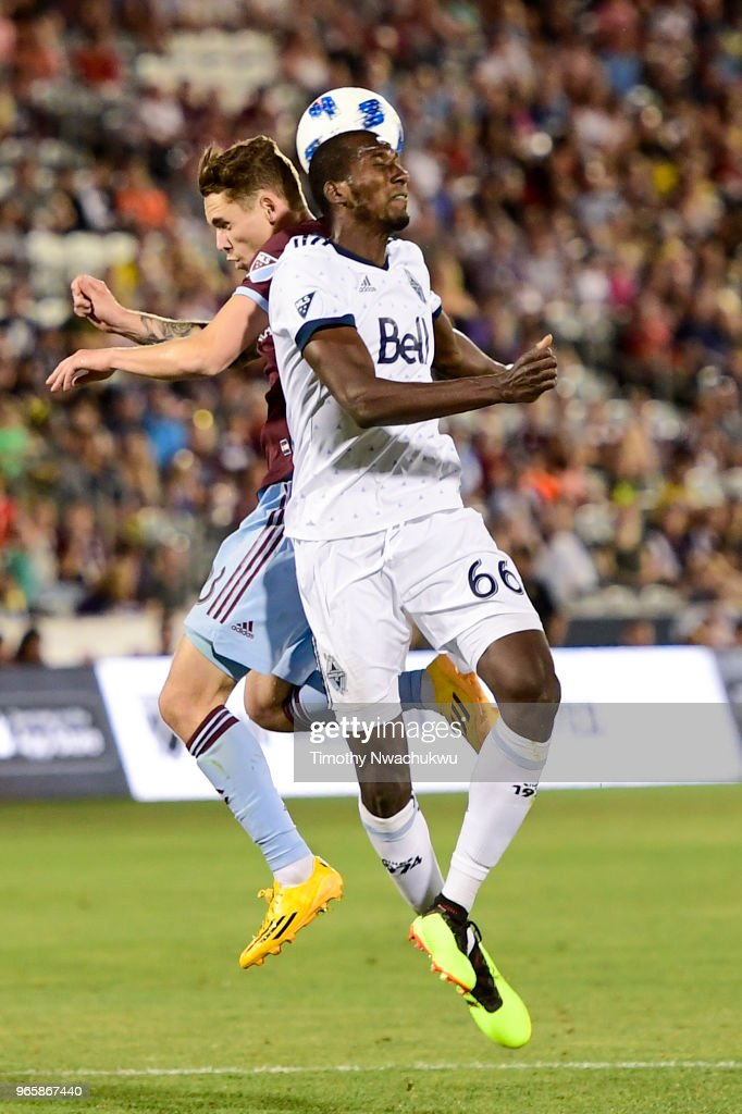 Zac MacMath #18 of Colorado Rapids and Ali Ghazal #66 of Vancouver Whitecaps reach for a header at Dick's Sporting Goods Park on June 1, 2018 in Commerce City, Colorado.