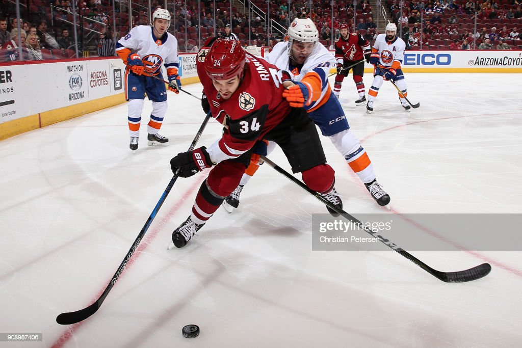 Zac Rinaldo #34 of the Arizona Coyotes skates with the puck ahead of Alan Quine #10 of the New York Islanders during the first period of the NHL game at Gila River Arena on January 22, 2018 in Glendale, Arizona.