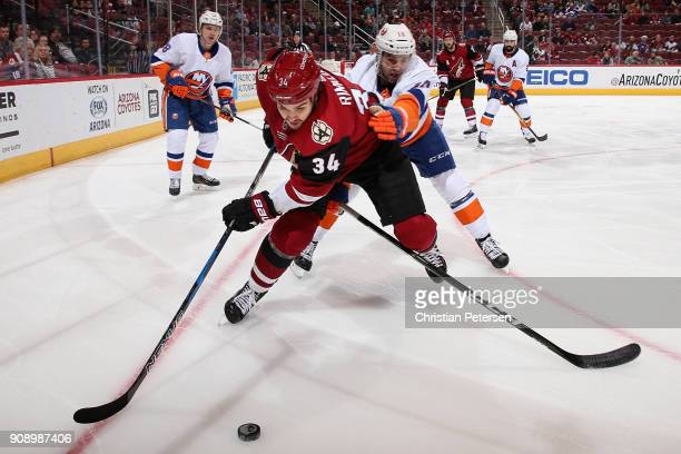 Zac Rinaldo of the Arizona Coyotes skates with the puck ahead of Alan Quine of the New York Islanders during the first period of the NHL game at Gila...